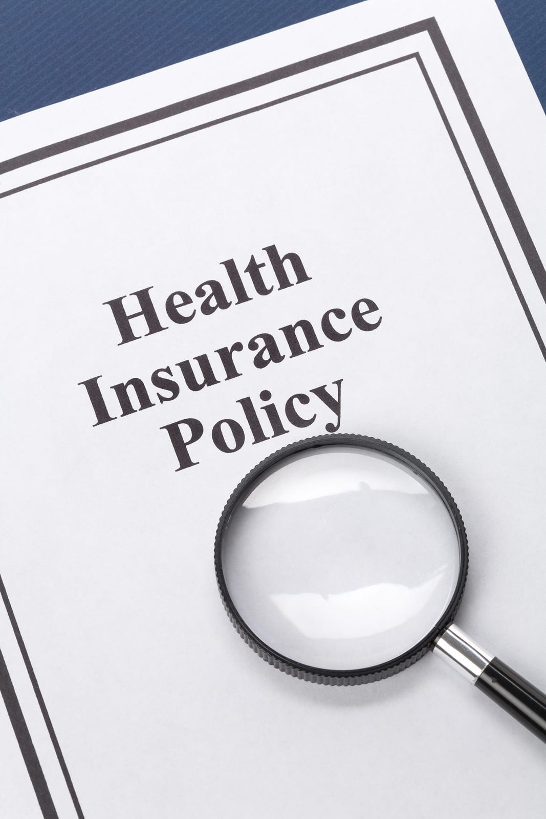 Magnifying glass set on a health insurance policy booklet.